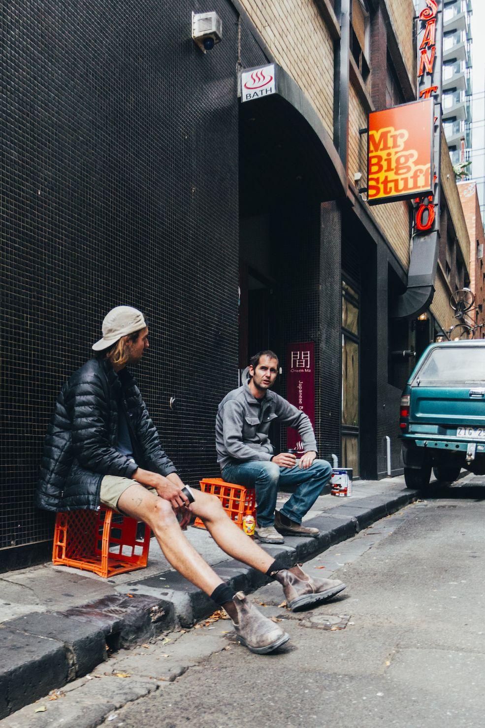 men sitting on sidewalk