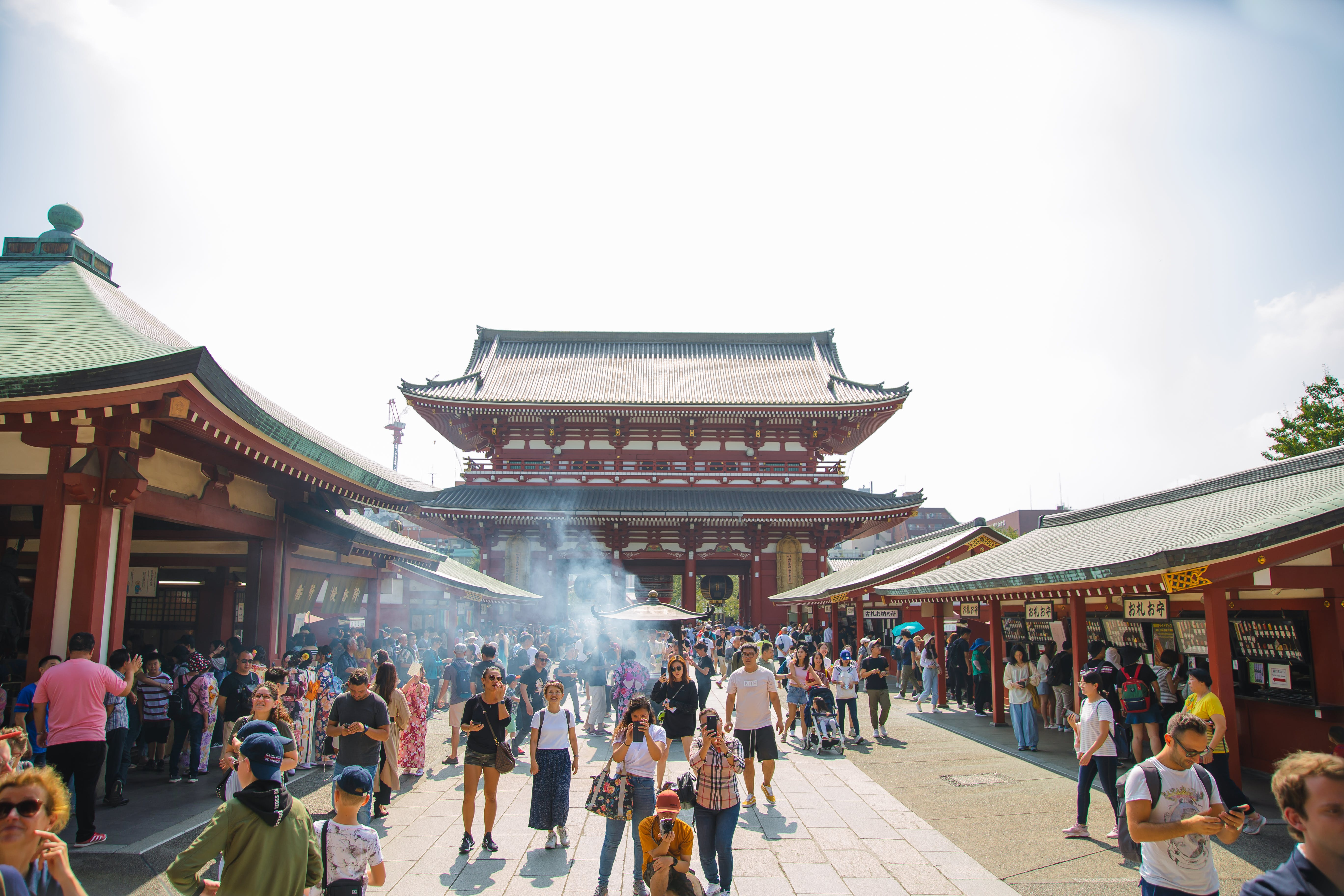 Unrecognizable tourists walking near old Buddhist temple in city